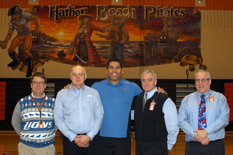 Former Detroit Lions defensive tackle Luther Elliss, poses with school administrators following a general assembly at Harbor Beach Community Schools.